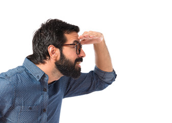 Young hipster man showing something over white background