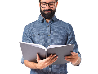 Young hipster man reading a book