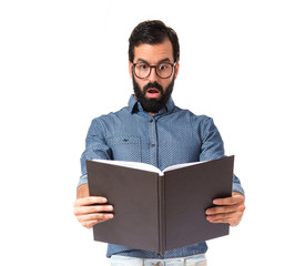 Surprised hipster man reading a book