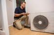 Focused handyman fixing air conditioning - 73838826