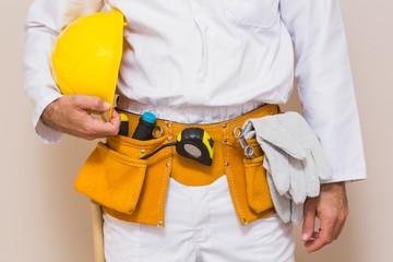 Handyman holding his yellow helmet in tool belt