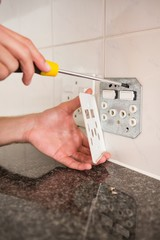 Electrician unscrewing face plate of plug socket