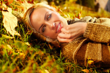 beautiful woman lying down on autumn leaves