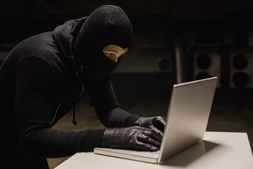 Robber at desk hacking a laptop