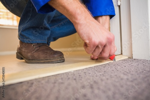 canvas print picture Handyman laying down a carpet