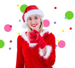 Composite image of festive blonde holding a mug