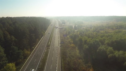 Fly over  highway with cars in sunny day and wood. Aerial