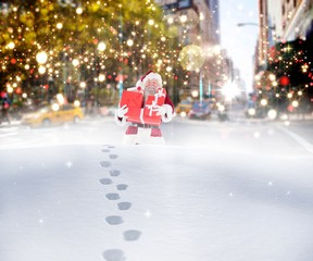 Composite image of santa carrying gifts in the snow