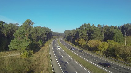 highway with cars in sunny day and wood. Aerial