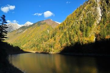 Mountain at Jiuzhaigou with contrastingly dark lake.