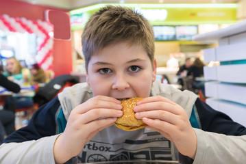 Teen boy eats  hamburger n Cafe