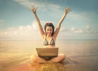 Happy technological girl at the beach