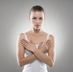 Young woman holding hands at her breast. Chest disease concept
