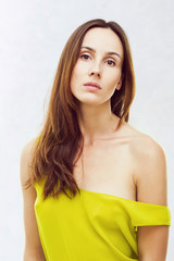 Portrait of a beautiful young girl in a yellow shirt on a white