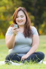 beautiful obese women playing mobile phone on the grass.