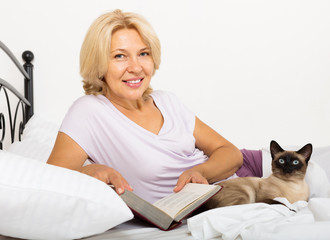 Mature woman with Siamese cat and book