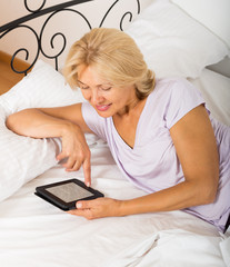 mature woman with ereader laying on bed