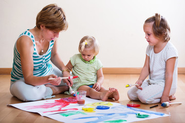 Mother and siblings painting with paints