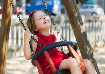 Laughing girl in red dres on  swing