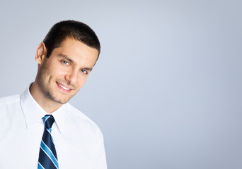 Happy smiling young businessman, against grey