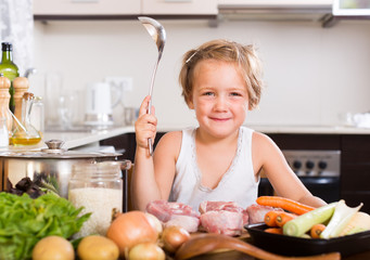 Baby girl cooking with meat