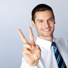 Businessman showing two fingers, against grey