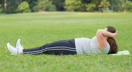 obese women sit ups on grass