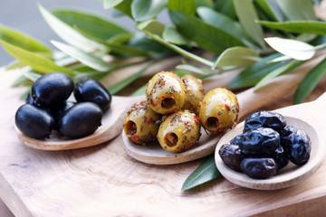 Verschiedene Oliven auf Olivenholz mit Olivenzweigen