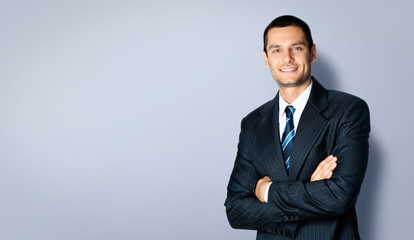 Happy businessman with crossed arms, against grey