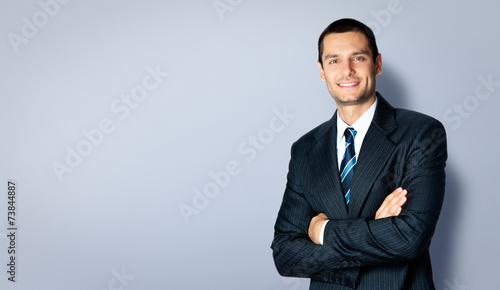 Happy businessman with crossed arms, against grey - 73844887