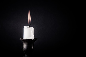 burning candle on a dark background