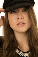 Female model touching her black hat close up