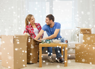 smiling couple opening cardboard box with dishes