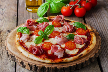 pizza with mozzarella and prosciutto, tomatoes