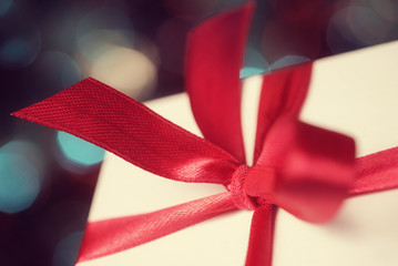 Macro of gift box with red bow against defocused lights