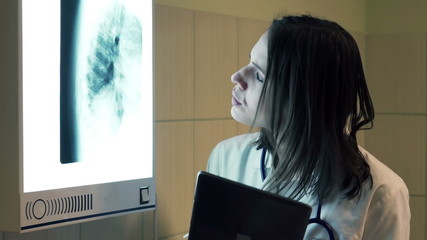 Female doctor checking lungs xray on tablet computer in hospital