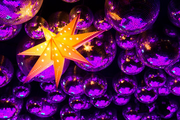 Nightclub disco balls and glowing star in festive lights