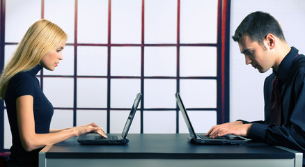 Young attractive smiling couple or business people on laptops wo