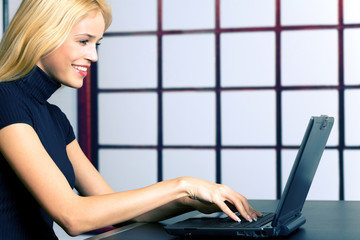 Young smiling businesswoman with laptop at office