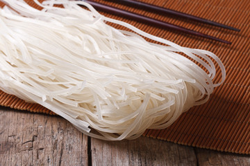 Dry rice noodles with chopsticks close up horizontal