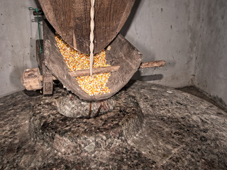 Milling corn, maize with grindstone. Traditional.