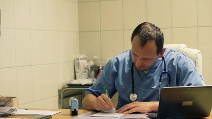 Male doctor writing rx prescription in hospital