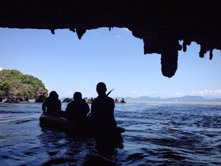silhouettes of kayakers in cave