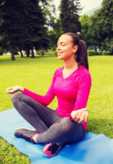 smiling woman meditating sitting on mat outdoors