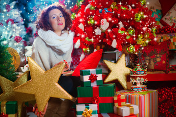 woman with a beautiful Christmas tree and gifts