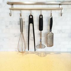 Kitchen utensils on a metal wall rail