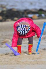 Enfant en train de jouer sur une plage de sable fin