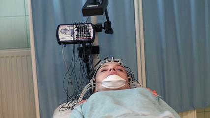 Woman in sleep having brain scan in hospital