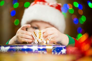 boy holding holiday ribbon on a present box