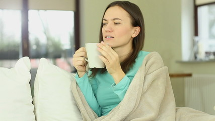 Happy female relaxing at home, drinking tea, using blanket